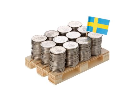 Swedish flag on the pallet with the Swedish coins isolated on white background. Stock Photo
