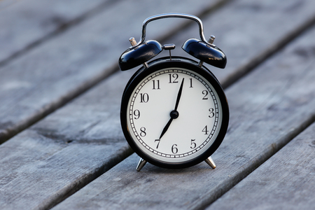 Black alarm clock with white dial on a table showsa few minutes past seven.