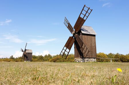 Two brown wooden windmills of subtype post mill on a field in the Swedish province of Gotland.