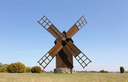 A brown wooden windmill on a field in the Swedish province of Gotland. Stock Photo