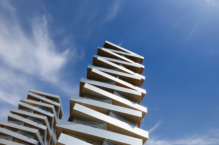 strive: Two modern  buildings stacked like pizza boxes strive towards the sky.