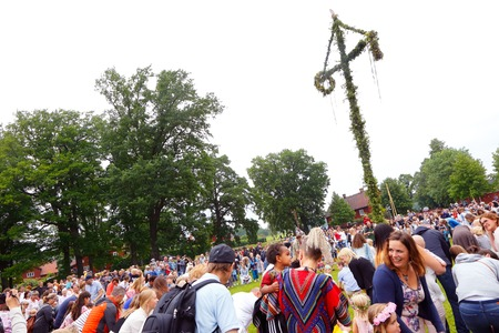 maypole: Mariefred, Sweden - June 24, 2016: Traditional midsummer celebrations on Midsummer Eve with public circle dance around the maypole. Editorial