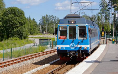 narrow gauge railway: Rydbo, Sweden - July 6, 2016: A blue passenger trains in traffic for SL on the narrow gauge railway Rolagsbanan with injenummer 28S with final destination Stockholm Ostra station at Rydbo station.