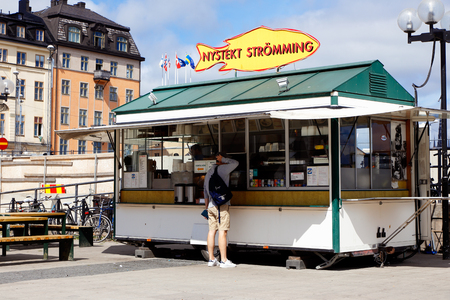 snack bar: Stockholm, Sweden - July 10, 2016: Customer at the snack bar with sale of freshly fried herring at Sodermalmstorg in Stockholm. Editorial