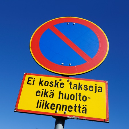 Finnish road sign parking prohibited with an additional panel, Does not apply to taxis and service vehicles, against blue sky.