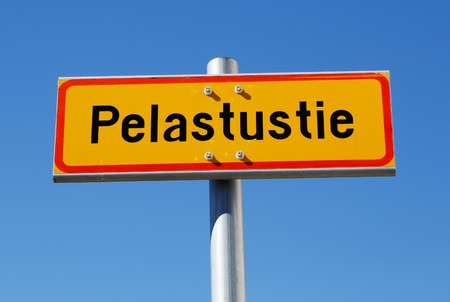 Finnish emergency exit sign (Pelastustie) in Finnish on a pole against blue sky. Stock Photo