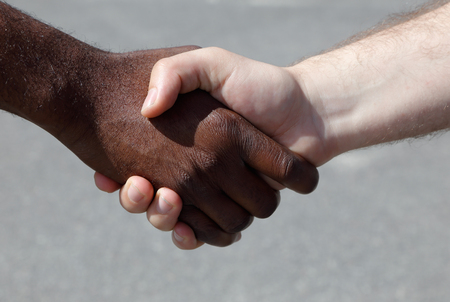 meet and greet: African and Caucasian men shaking hands outdoors.