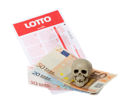 Skull on top of Euro banknotes placed on top of a Finnish Veikkaus game of chance Lotto lottery ticket isolated on white background.