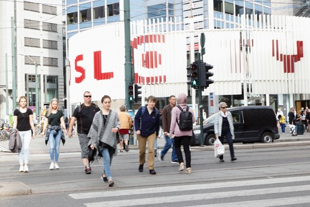 Oslo, Norway - September 16, 2016: People crossing the street on the crosswalk outside Oslo City shopping center seen in the background.