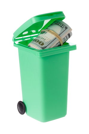One green recycling bin with an open lid and a roll of dollar bills inside isolated on white backlground.