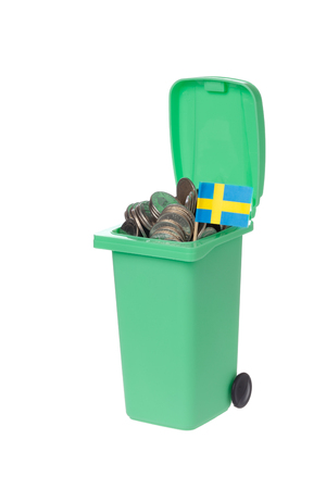 wasted: Green recycling bin with coins and Swedish flag isolated on white background.