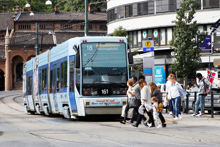 Oslo, Norway - September 16, 2016: A blue articulated tram of class SL95 in service on line 18 at the stop on the street Biskop Gunnersen gate in downtown Oslo with people crossing the street at the rear of the street car.