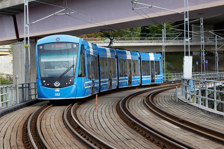 Lidingo, Sweden - September 25, 2016: Blue articulated tram of type A36 in service for SL enters the Old Lidingo bridge on the rapid rail line Lidingobanan near the the final destination Ropsten in Stockholm.