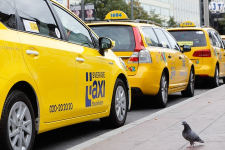 Stockholm, Sweden - September 25, 2016: A row of yellow taxi cabs parked at the taxi stand outside the Stockholm Central station. Editorial