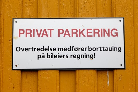 parking violation: Norwegian sign on a yellow wooden wall informs that it is a private parking and violation results in removal at the owners expense.