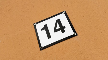 fourteen: A house number sign with number fourteen isolated on a brown colored wall. Stock Photo
