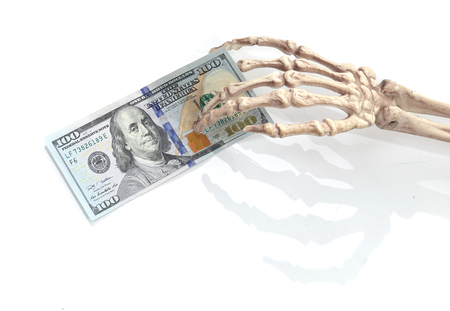 meth: Skeleton hand holding a 100 US dollar bank note on white.
