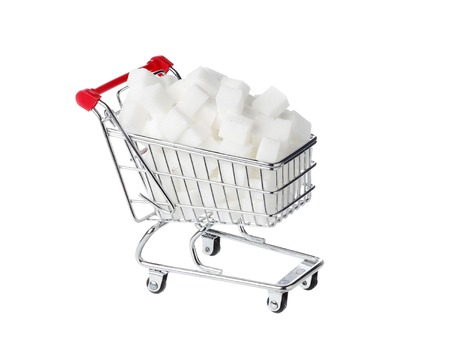 shopping binge: One shopping cart filled with sugar cubes isolated on white.