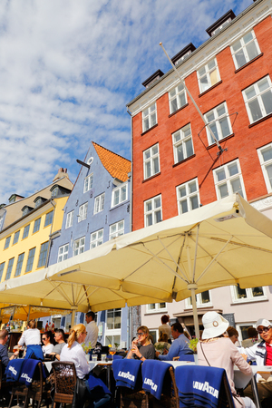 Copenhagen, Denmark - August 24, 2017: Restaurant guests at the outdoor seating in Nyhavn in front of the colorful old builds in the background. Editorial