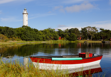 The lighthouse named Lange Erik with small fishing boat in the forground at the north end of the Swedish island Oland.