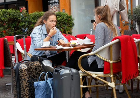 Copenhagen, Denmark - August 24, 2017: Two young women with suitcases sitting at an outdoor table at a restaurant in Nyhavn enjoying breakfast. Editorial