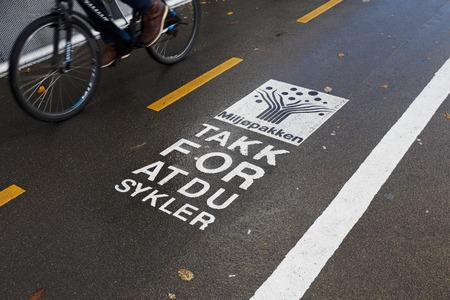 Trondheim, Norway - October 16, 2017: One bicycle passing a sign on the bicycle track with a message fromm the Tronheim enviroment project Miljopakken, with text in Norwegian translated to English reading, Thanks for cycling.