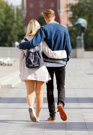 Stockholm, Sweden - July 31, 2015: A pair walks with their arms around each other near the National museum.