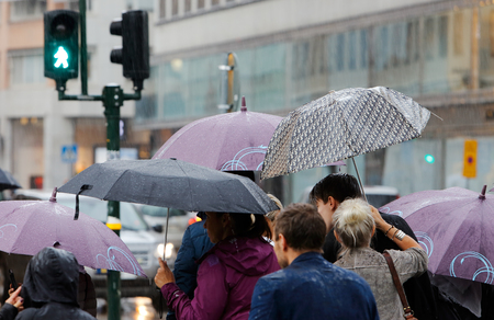 Stockholm, Sweden - July 29, 2015: People in the rain with umbrellas at a crosswalk in downtown Stockholm Editorial