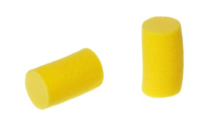 Two noise cancelling yellow foam ear plugs isolated on white background.
