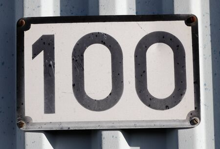 A house number faded plate with number 100.
