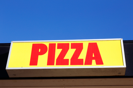 Pizza sign with red text on yellow background with blue sky above.