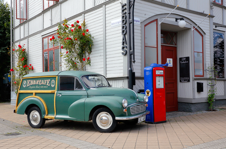 Borgholm, Sweden - August 22, 2017: A green Morris Minor 1000 of the 1965 model parked outside the STF hostel and restaurant Ebbas at the street Storgatan.
