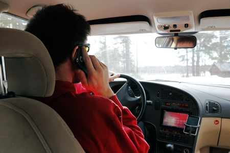 Ranea, Sweden - March 29, 2014: The driver uses a handheld mobile phone while driving the car.