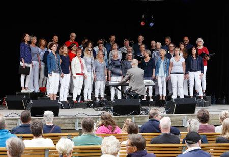 Strangnas, Suécia - 20 de maio de 2017: cantando o coro Lovsangarna executa para uma audiência em uma fase exterior no parque de Ugglans durante o evento da cultura de Kultur 17.