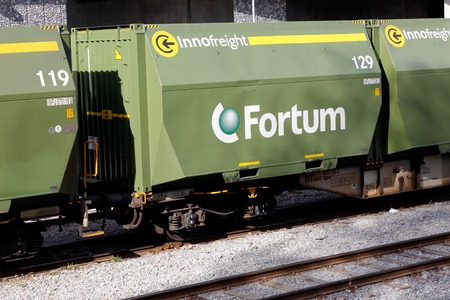 Stockholm, Sweden - May 16, 2017: Green railroad container freight cars of class Sgnss with containers intended for transport of wood chips as fuel near the Fortum power plant at Vartan