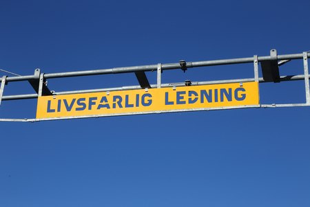 Swedish sign informs at a railroad  level crossing about the dangerous high voltage overhead line.