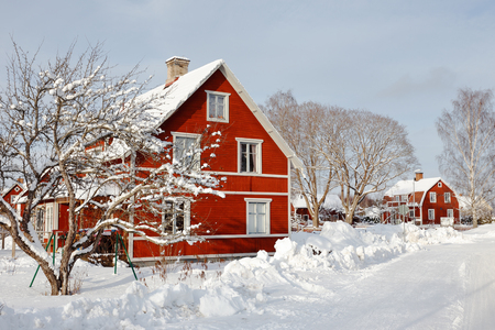 Swedish red two storeywooden  family houses behind a snow covered tree alongside the snow surfaced road in the residential area during the winter season. Stock Photo