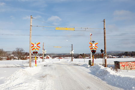 Gagnef, Sweden - February 9, 2018: Swedish railroad crossing with bars, sound and light signals in the countryside during winter time.