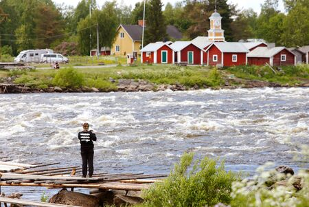 Kukkola, Finland - JUly 3, 2017: A tourist with a camera at the Kukkola rapids in the Torne river at the Finno-Swedish border. Sajtókép