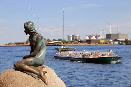 Copenhagen, Denmark - June 27, 2018: The statue of the Little Mermaid, by Edvard Eriksen, located at Langelinie, with sightseeing boats behind. Editorial