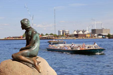 Copenhague, Danemark - 27 juin 2018 : La statue de la Petite Sirène, d'Edvard Eriksen, située à Langelinie, avec des bateaux touristiques derrière. Éditoriale