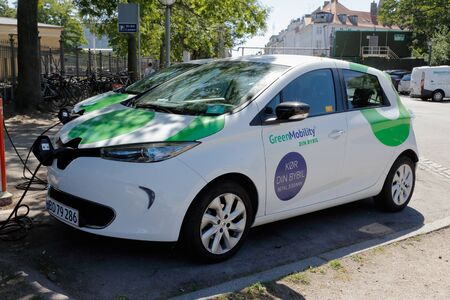 Copenhagen, Denmark - June 27, 2018: Parked electric car with its charing cable connected. Editorial