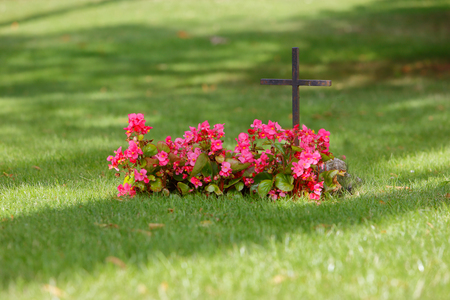A christian grave with red flowers marked with an iron cross in the lawn. Stock fotó