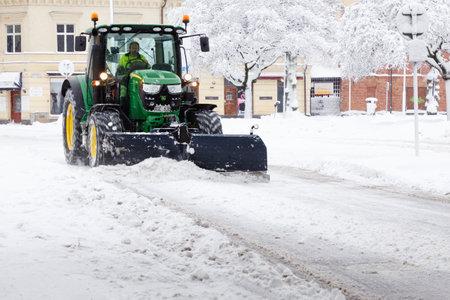 Sodertalje, Sweden - February 2019: Green John Deere tractor plowing snow on the Storgatan street.