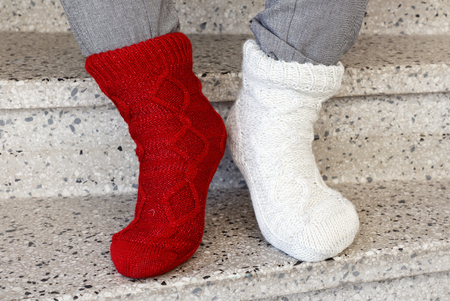 Close up of the feet wearing socks in different color on each foot.