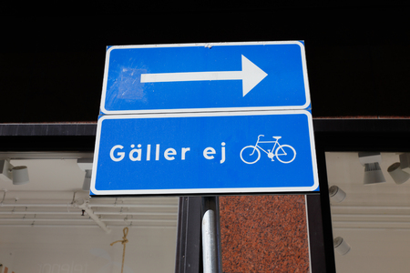 Swedish one-way road sign with an exception for bicycles.