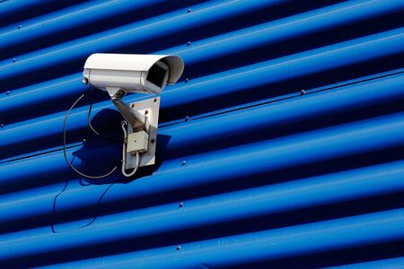Security camera mounted on blue wall of corrugated sheet.