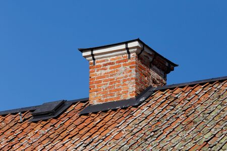 Low angle view of a red brick chimney on a roof.