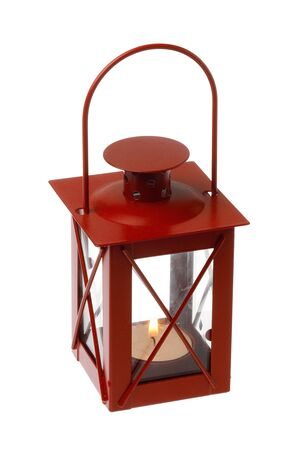 Red colored decorative metalic small lantern with a lit tealight inside isolated on white background.