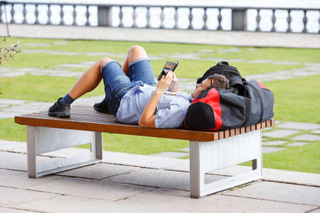 Stockholm, Sweden - July 31, 2020: A young man is lying on a park bench with a bag as a pillow in the city hall park and using his mobile phone. 新闻类图片